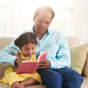 Parent Sitting on a Couch Reading to a Small Child